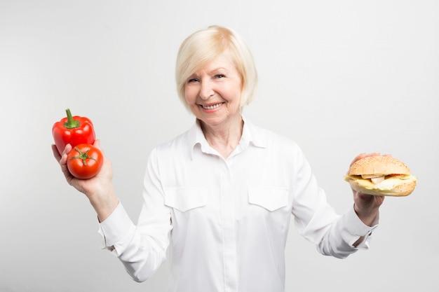 Ein bild des dilemmas, das diese dame hat. auf der einen seite gibt es eine gute und gesunde mahlzeit und auf der anderen seite einen leckeren, aber nicht gesunden hamburger. auf weißem hintergrund isoliert