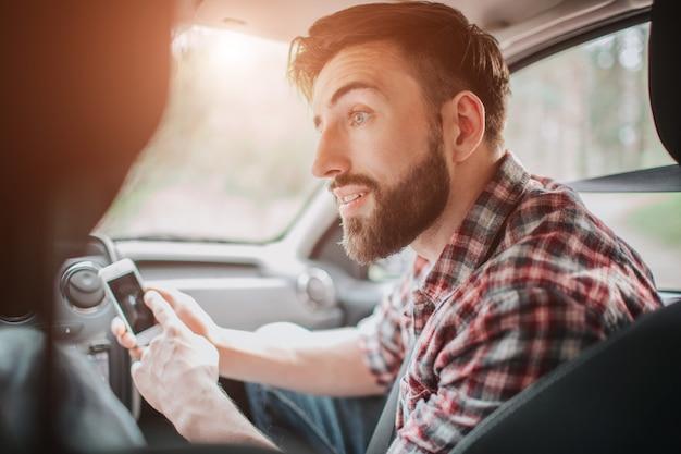Ein bild des kerls, der auf sitz im auto sitzt und kleines und weißes telefon hält. er ist auf einem dunklen bildschirm und schaut nach links. er ist ein bisschen besorgt.