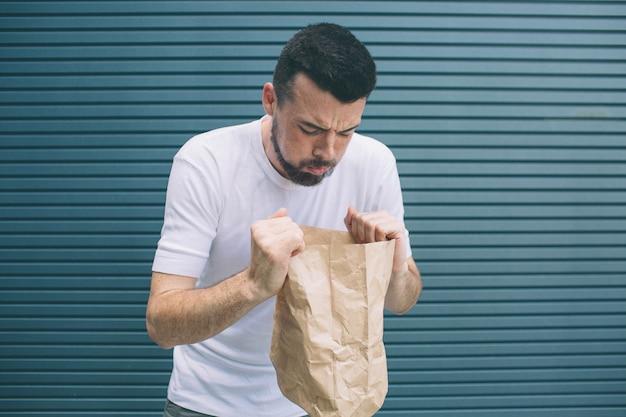 Ein bild des kranken mannes, der versucht, sich in papiertüte zu übergeben. er fühlt sich schrecklich. isoliert auf gestreift