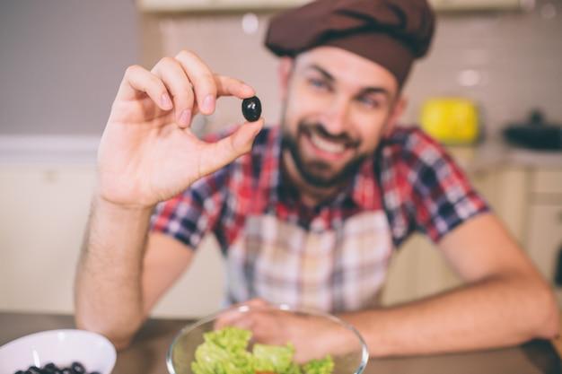 Ein bild des positiven und bärtigen mannes, der auf tabelle sich lehnt und ein stück schwarze olive hält. er sieht es an. darauf konzentriert sich der junge mann