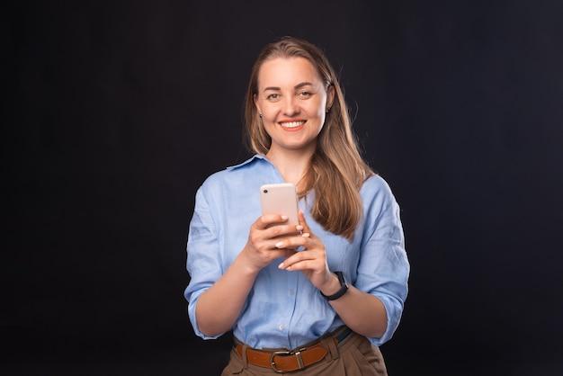 Ein bild einer fröhlichen frau, die in die kamera lächelt und mit jemandem auf ihrem handy chattet