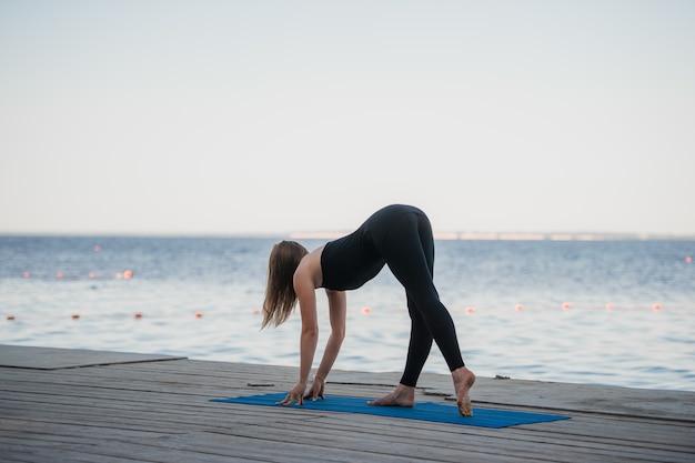 Ein bild einer hübschen frau, die yoga am see tut