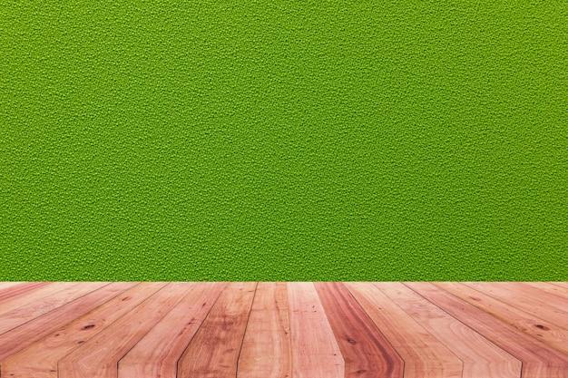 Ein bild eines hölzernen schreibtisches vor einem abstrakten hintergrund des grünen stoffes.