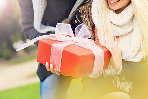 Ein bild eines jungen paares mit geschenk im park