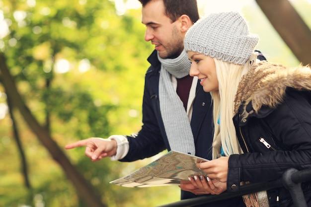 Ein bild eines jungen paares mit karte im park