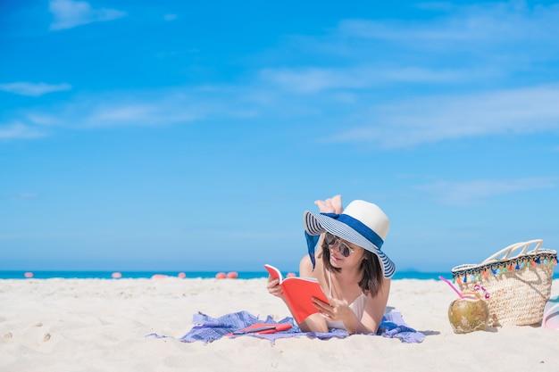 Ein bild eines mädchens, das auf dem strand ein buch lesend sich entspannt.