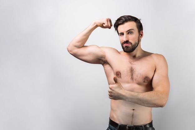 Ein bild eines toplessen mannes, der an der weißen wand steht und ein spiel der muskeln von seiner rechten hand zeigt. er sieht unglaublich und mächtig aus. schnittansicht.