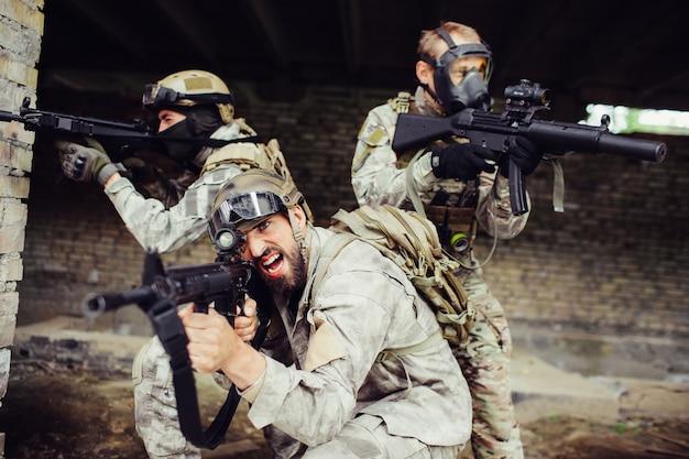 Ein bild von drei typen posiert. zwei von ihnen haben schwarze masken im gesicht. sie schauen und zielen auf verschiedene seiten. sie verteidigen sich.