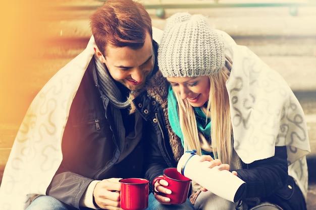 Ein bild von einem jungen paar, das draußen tee trinkt