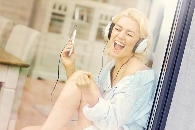 Ein bild von einer jungen frau, die zu hause musik hört