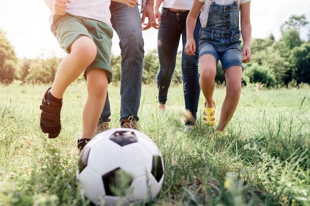 Ein bild von familienbeinen, die auf wiesengras aufwachen. sie spielen fußball. vor den beinen der menschen befindet sich ein spielball.