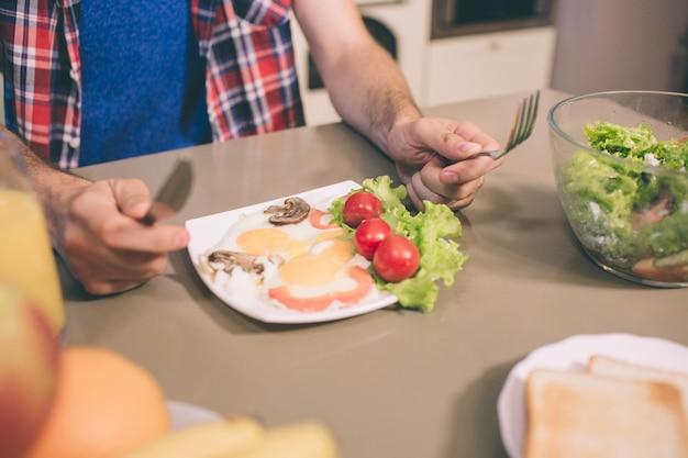 Ein bild von leckerem omelett mit letuce und kirschtomaten auf teller auf tisch. guy hält messer und gabel in den händen. er ist bereit, es zu essen.