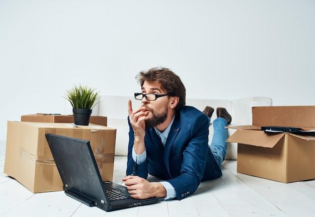 Ein billiger mann liegt auf dem boden vor einem laptop-bürowechselarbeitsplatz