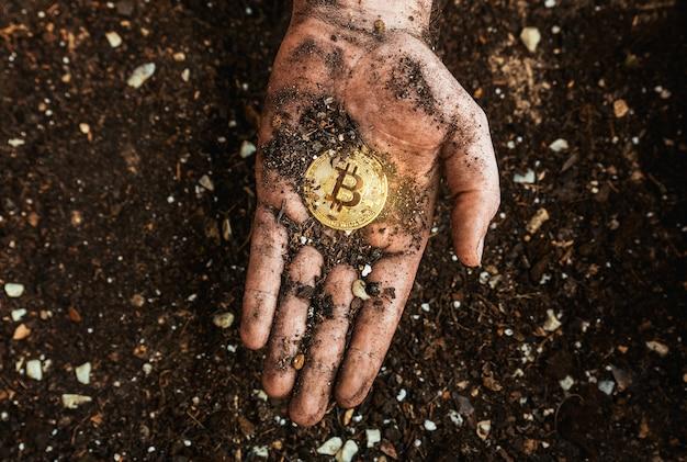 Ein bitcoin auf dem boden in einer schmutzigen hand