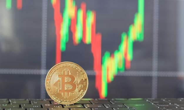 Ein bitcoin auf der tastatur und eine grafik des wachstums und preisverfalls