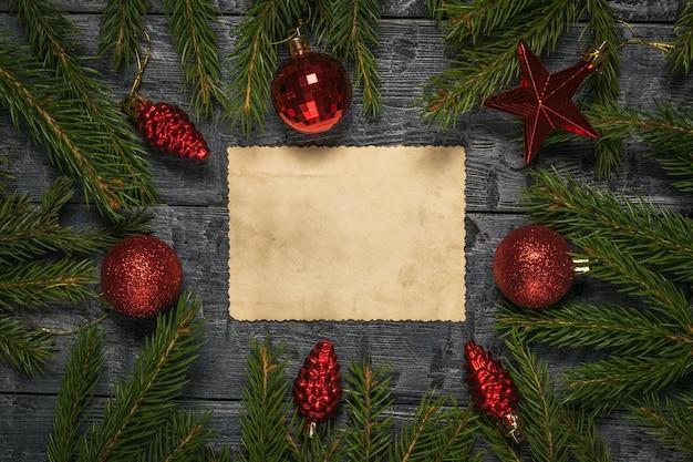 Ein blatt altes papier in der mitte des tisches zwischen den zweigen eines tannenbaums und glasspielzeug