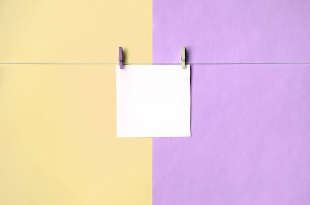 Ein blatt papier hängt an einem seil mit klammern auf beschaffenheitshintergrund von gelben und violetten modepastellfarben
