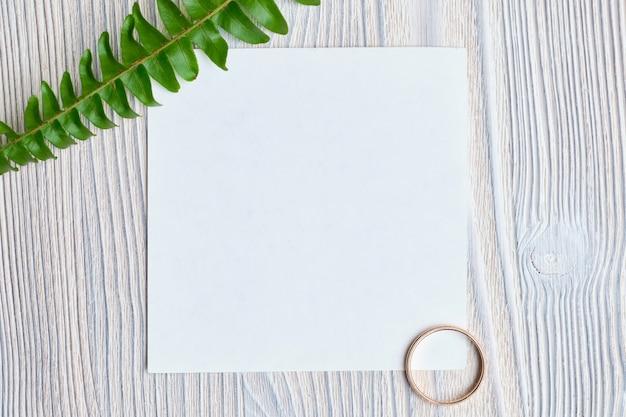 Ein blatt papier mit einem grünen zweig und einem goldenen ehering. das konzept einer liebeserklärung. draufsicht.
