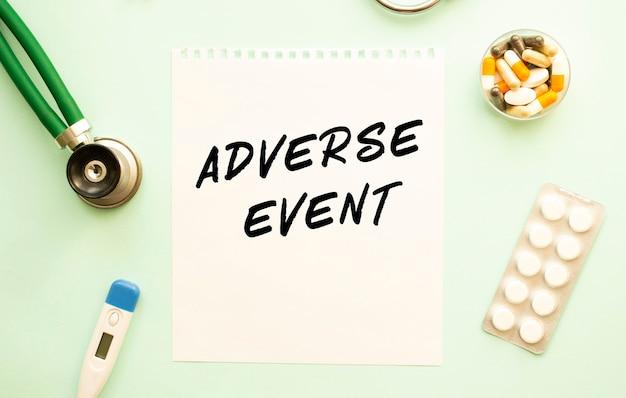 Ein blatt papier mit text adverse event, stethoskop und medikamenten
