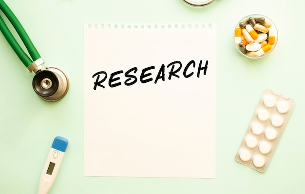 Ein blatt papier mit text research stethoskop und medikamente