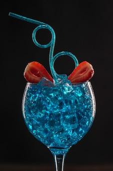 Ein blau gefärbter cocktail in einem eisglas, dekoriert mit limette und erdbeeren mit einem lockigen trinkhalm