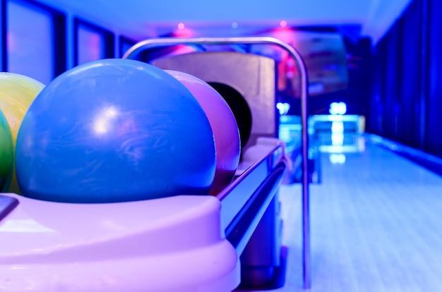 Ein blauer bowlingball ist bereit für den spieler, um den ball auf der holzbahn zu werfen