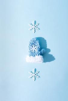 Ein blauer fäustling und zwei weiße schneeflocken, sonnenlicht, draufsicht.