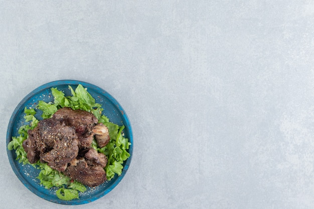 Ein blauer holzteller mit gebratenem fleisch und geschnittenem salat.