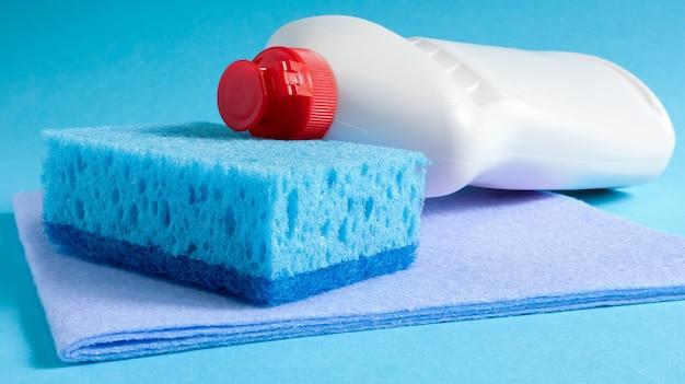 Ein blauer schwamm mit einer weißen flasche waschmittel auf einem blauen hintergrund.