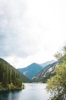Ein blauer see zwischen bergen und bäumen an einem sommertag.