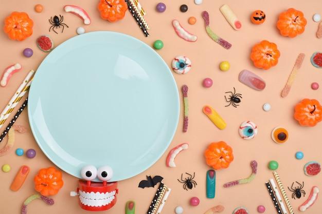 Ein blauer teller auf dem hintergrund verschiedener süßigkeiten auf einem orangefarbenen hintergrund mit einem platz für text. hintergrund für den halloween-urlaub. flaches layout, draufsicht, ein ort zum kopieren.