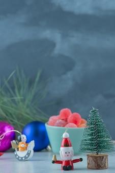 Ein blauer teller marmelade mit kleinen weihnachtsfestspielzeugen auf marmorhintergrund. hochwertiges foto