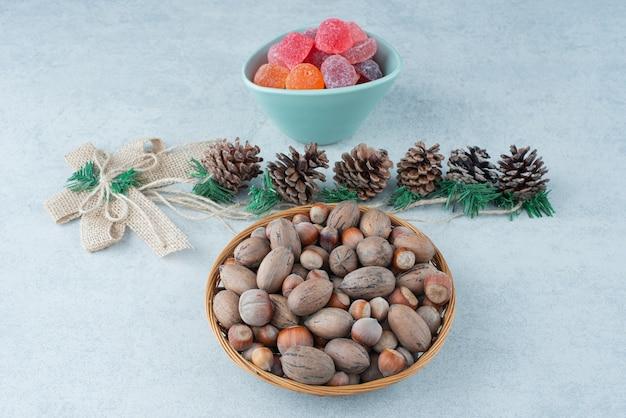 Ein blauer teller marmelade mit kleinen weihnachtstannenzapfen auf marmorhintergrund. hochwertiges foto