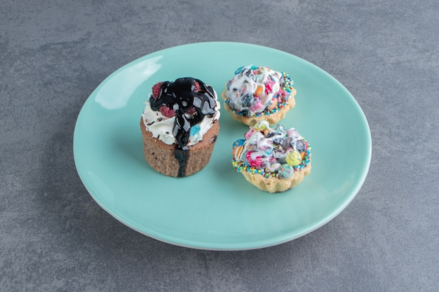 Ein blauer teller mit drei süßen cupcakes mit streuseln
