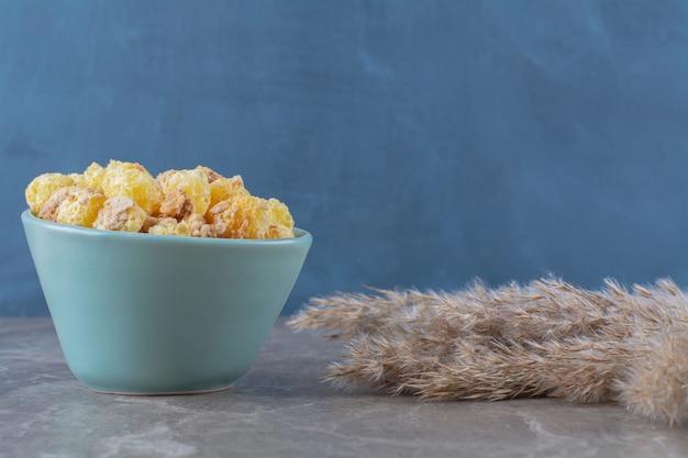 Ein blauer teller mit gesunden süßen cornflakes auf grau