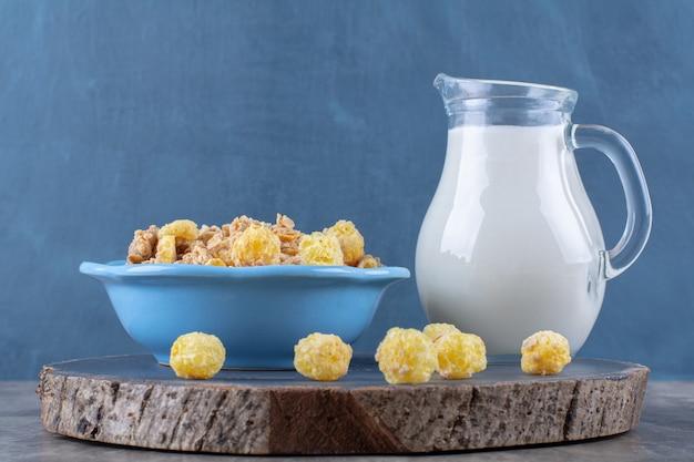 Ein blauer teller mit gesunden süßen cornflakes mit einem glas milch auf einem holzstück.
