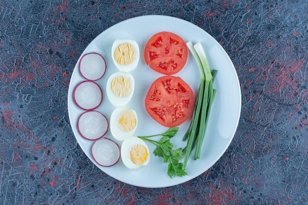 Ein blauer teller mit hartgekochten eiern mit gemüse.