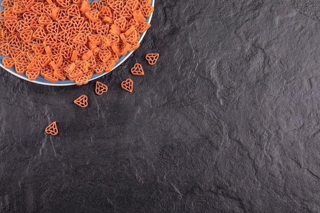 Ein blauer teller mit roher pasta in herzform auf schwarzem tisch