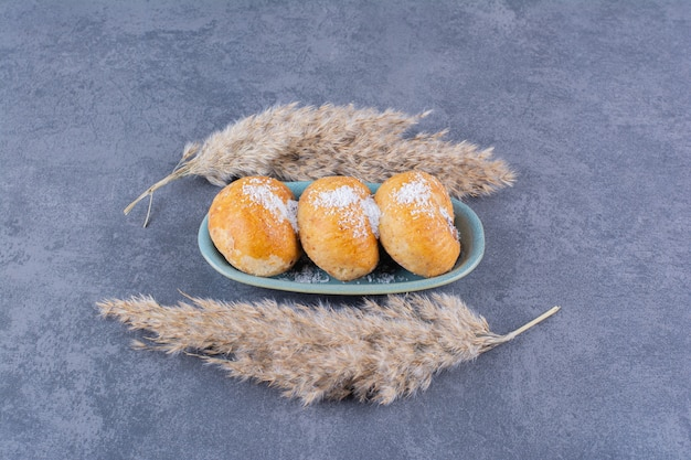 Ein blauer teller mit süßen kuchen mit zucker- und weizenähren auf stein.