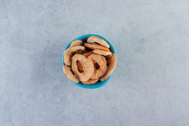 Ein blauer tiefer teller mit gesunden trockenfrüchten auf marmorhintergrund.