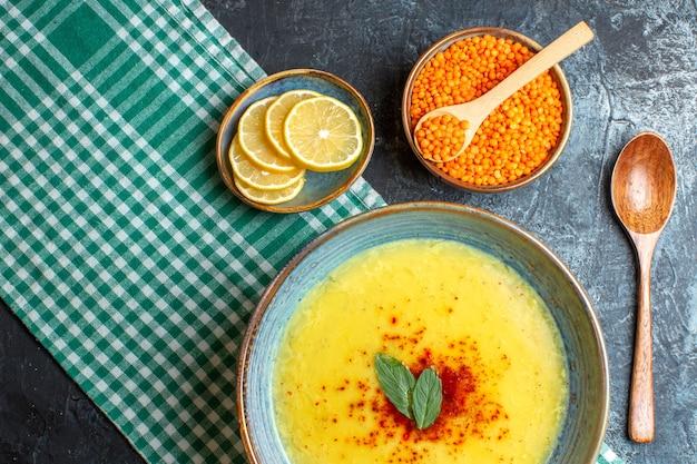 Ein blauer topf mit leckerer suppe, serviert mit minze und pfeffer auf einem abgestreiften handtuch