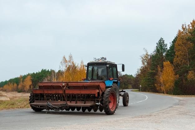 Ein blauer traktor mit einem anhänger für landwirtschaftliche arbeiten fährt