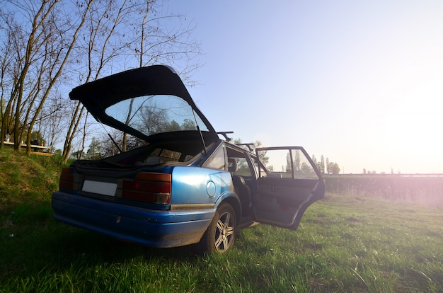 Ein blaues auto auf einem hintergrund einer rustikalen landschaft mit einem wilden stockfeld und einem kleinen see. die familie kam in der nähe des sees zur ruhe