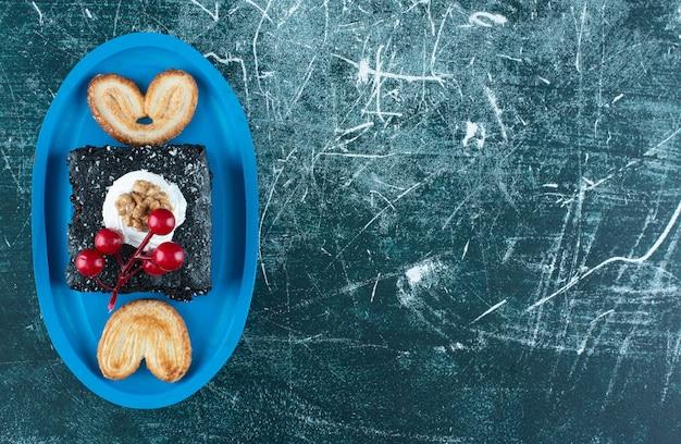Ein blaues brett mit einem stück schokoladenkuchen und keksen. foto in hoher qualität