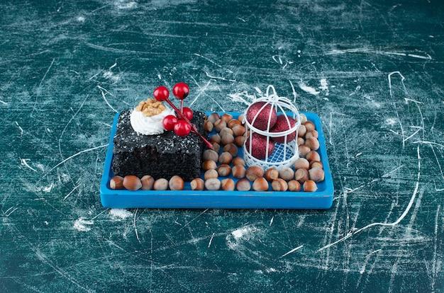 Ein blaues brett mit einem stück schokoladenkuchen und macadamianüssen. foto in hoher qualität