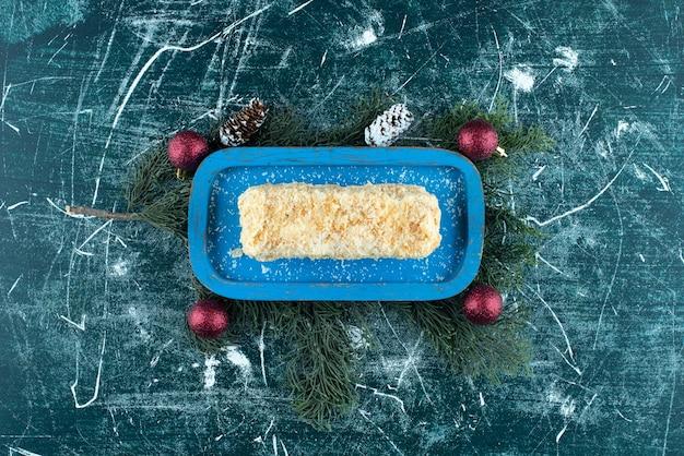 Ein blaues brett mit süßem brötchenkuchen und weihnachtskiefernzapfen. foto in hoher qualität