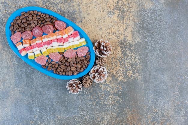 Ein blaues brett voller verschiedener fruchtgelee-bonbons mit tannenzapfen. hochwertiges foto