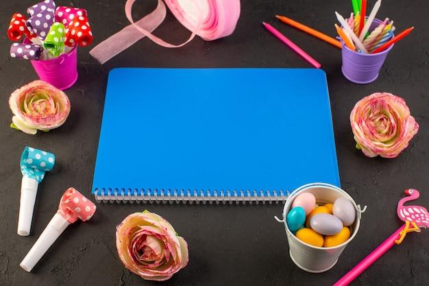 Ein blaues heft der draufsicht mit verschiedenen dekorationen auf dem bonbonfarbfoto des dunklen schreibtischbuchs