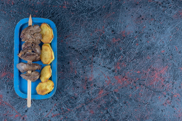 Ein blaues holzbrett aus bratkartoffeln mit fleisch