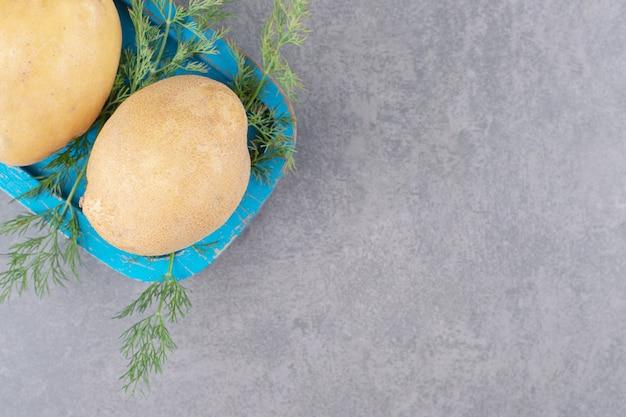 Ein blaues holzbrett aus ungekochten kartoffeln mit frischem dill.